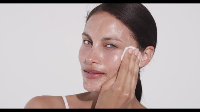 Woman wipes off excess exfoliater with cotton pad