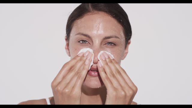 woman wipes off excess exfoliater with cotton pads - exfoliation stock videos & royalty-free footage
