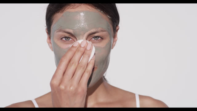Woman wipes off excess face mask with cotton pad