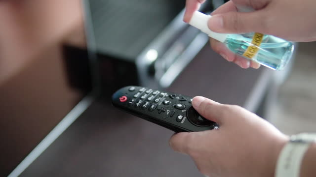woman wiping down remote control with disinfection wipes. - rubbing alcohol stock videos & royalty-free footage