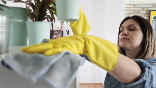 woman wiping dust from furniture at home during lockdown - washing up glove stock videos & royalty-free footage