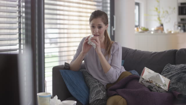 Woman wiping her nose watching a sad movie