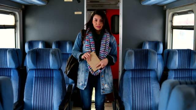 frau mit einem rucksack zu fuß in wagen im zug - bahnreisender stock-videos und b-roll-filmmaterial