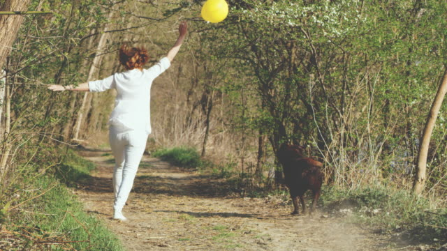 SLO MO Woman with a balloon running with her dog in the forest