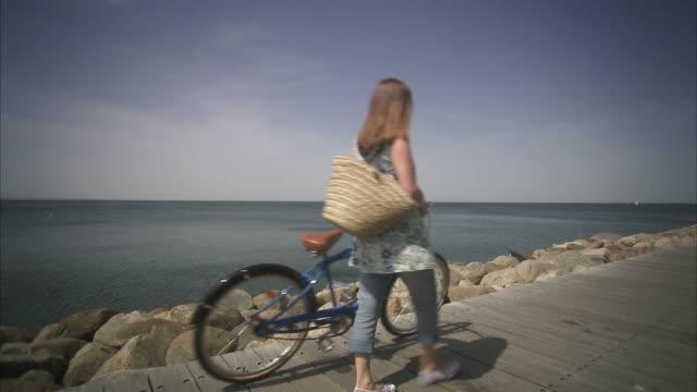 A woman with a bike walking on a jetty Skane Sweden.