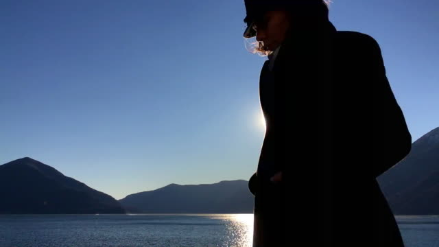 Woman with a Coat and Hat Passing By in Front of Sun in Sunset on Alpine Lake with Mountain
