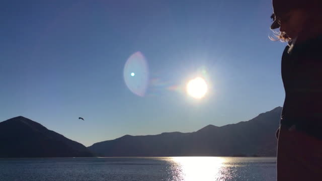 woman with a coat and hat passing by in front of sun in sunset on alpine lake with mountain - オーバーコート点の映像素材/bロール