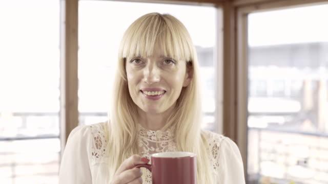vídeos y material grabado en eventos de stock de a woman with a cup and a hot drink against a city urban skyline. - esmalte de uñas rojo