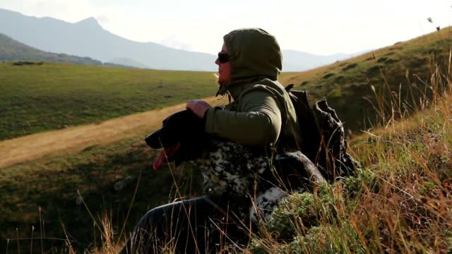 Eine Frau mit einem Hund sitzt auf einem Hügel