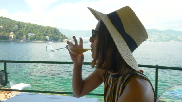 A woman with a glass of white wine at a restaurant overlooking the Mediterranean Sea in Italy, Europe. - Slow Motion