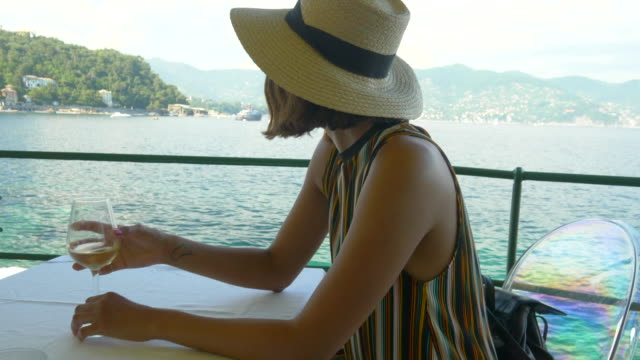 a woman with a glass of white wine at a restaurant overlooking the mediterranean sea in italy, europe. - slow motion - solitude stock videos & royalty-free footage