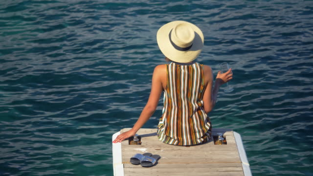 A woman with a glass of white wine on a dock over the Mediterranean Sea in Italy, Europe. - Slow Motion