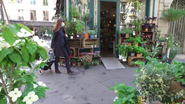 woman, with a protective mask, goes shopping for food, walk in front of a florist, on may 13, 2020 in paris, france. france has started a progressive... - 45 49 years stock videos & royalty-free footage