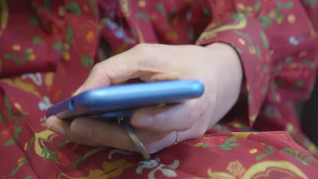 vidéos et rushes de femme avec une robe rouge, utiliser un smartphone pour communiquer avec son ami sur un réseau social - robe rouge