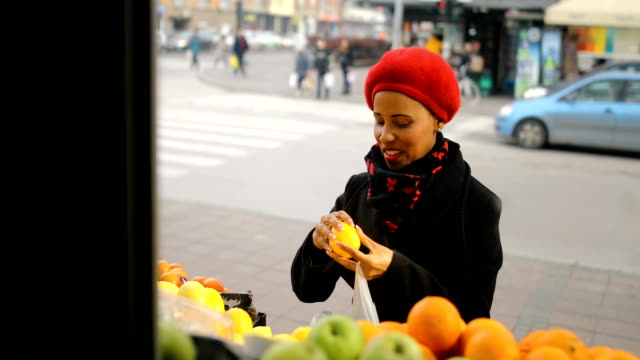 woman with a red hat choosing fruits on street market - bag stock videos & royalty-free footage