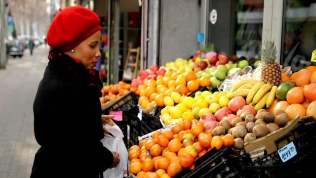 ストリートマーケットで果物を選ぶ赤い帽子をかぶった女性 - ファーマーズマーケット点の映像素材/bロール