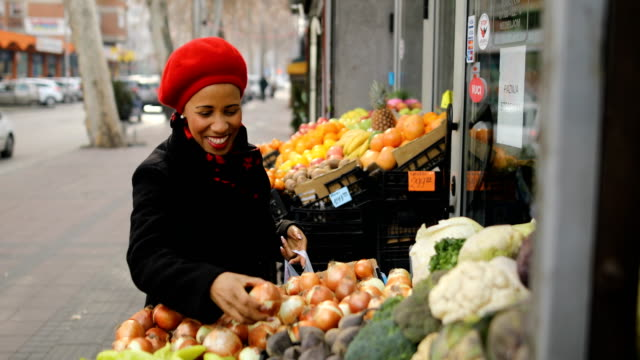 woman with a red hat choosing vegetables on street market - onion stock videos & royalty-free footage
