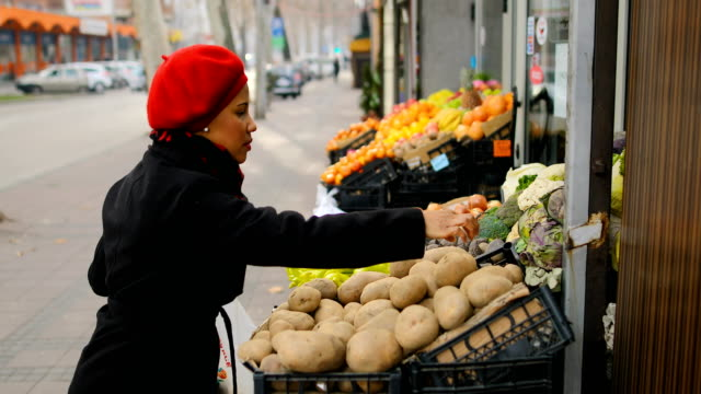 woman with a red hat choosing vegetables on street market - hat stock videos & royalty-free footage
