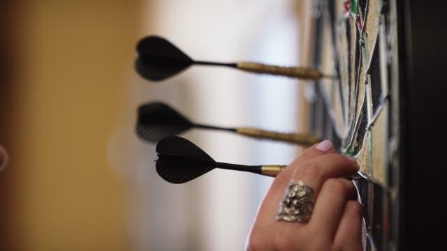 ダーツボードからリングとピンクの爪ポーランド語引きダーツを持つ女性 - ダーツバー点の映像素材/bロール
