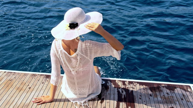slo mo woman with a sunhat sitting on the stern - sun hat stock videos & royalty-free footage