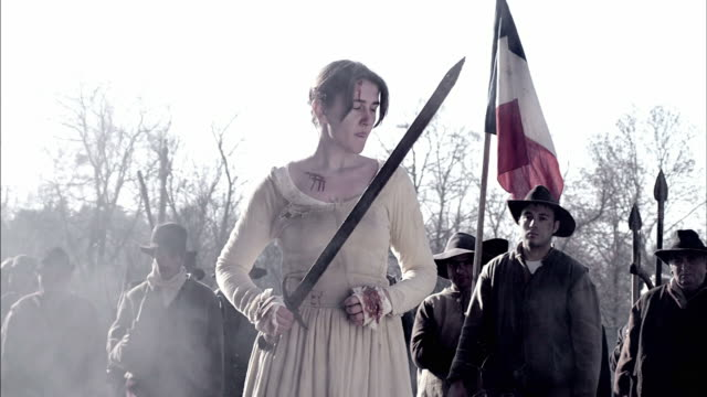 A woman with a sword looks back at soldiers with weapons during a reenactment of the Storming of the Bastille.