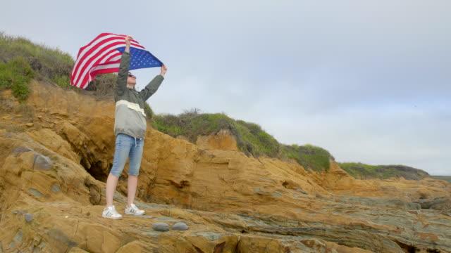 太平洋の野生の海岸の岩の上にアメリカの旗を持つ女性。カリフォルニア。 - アメリカ憲法点の映像素材/bロール