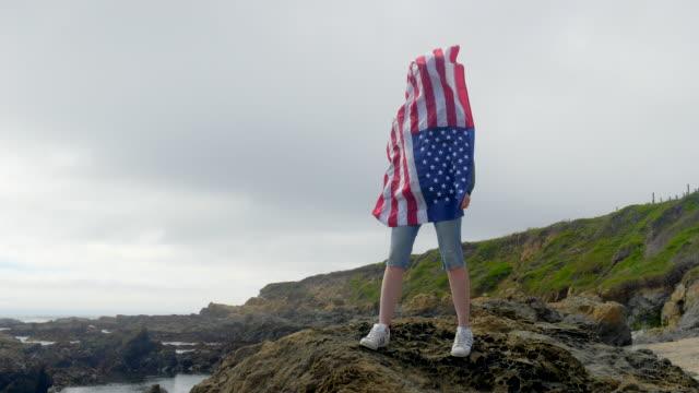 vídeos de stock, filmes e b-roll de mulher com a bandeira americana nas rochas da costa selvagem do oceano pacífico. califórnia. - partido político