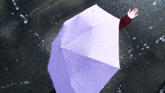 woman with an umbrella standing in the rain - レインコート点の映像素材/bロール