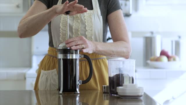 vídeos de stock e filmes b-roll de woman with apron presses the french coffee press - chaleira de chá
