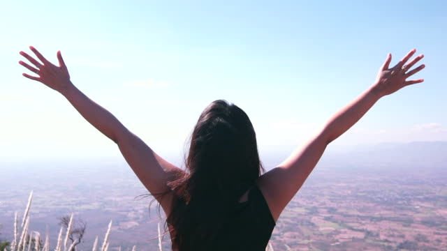 woman with arm raised on top of mountain