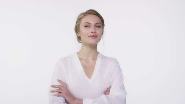 woman with arms crossed against white background - arms crossed stock videos & royalty-free footage