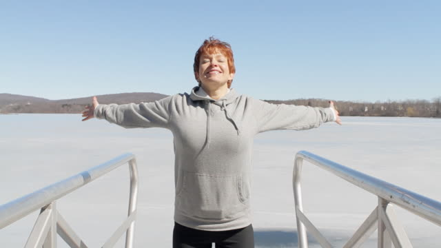 MS Woman with arms outstretched by frozen lake / Glen Gardner, New Jersey, USA