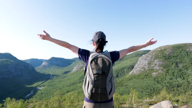 woman with arms raised hiking to mountain peak at parc national des grands-jardins, quebec, canada - rucksack stock videos & royalty-free footage