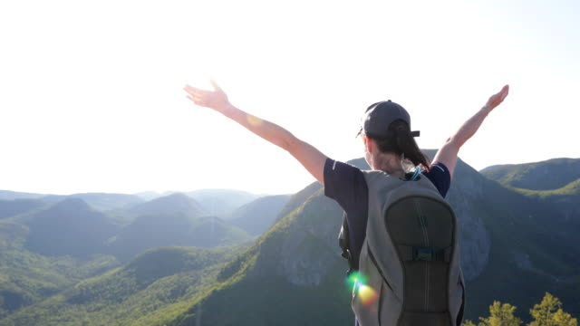 woman with arms raised hiking to mountain peak at parc national des grands-jardins, quebec, canada - parc national stock videos & royalty-free footage