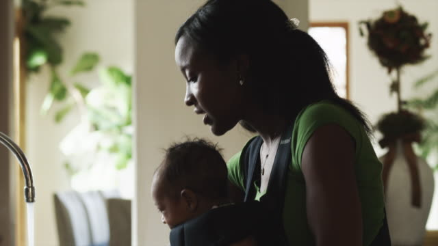 ms tu td woman with baby boy (2-5 months) in kitchen / cedar hills, utah, usa - baby carrier stock videos & royalty-free footage