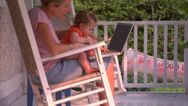 vidéos et rushes de tu, zo, ms, woman with baby girl (12-17 months) and laptop on laps sitting on porch, st. simons, glynn county, georgia, usa - 12 17 mois