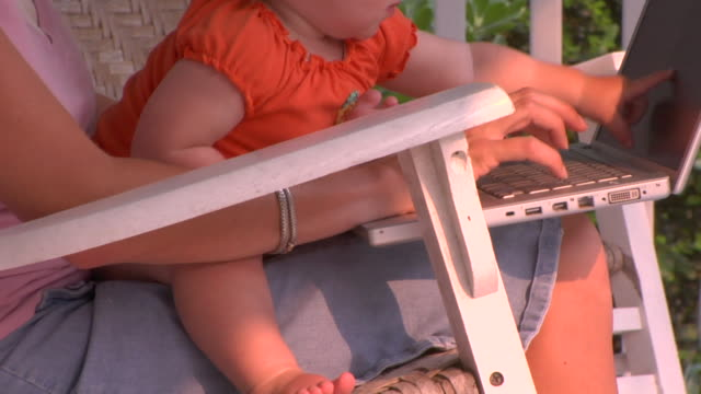 cu, tu, zo, woman with baby girl (12-17 months) and laptop on laps sitting on porch, st. simons, glynn county, georgia, usa - 12 17 months stock videos & royalty-free footage