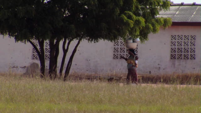 ws woman with baby in carrier on back carrying pots on head, tamale, ghana - baby carrier stock videos & royalty-free footage
