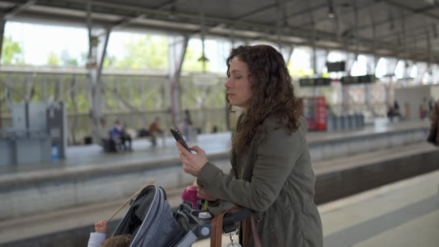 woman with baby stroller waiting on a train platform checking phone - station stock videos & royalty-free footage