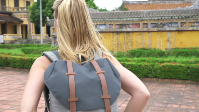 Woman with backpack explores temple