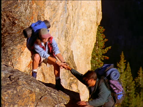 Woman with backpack helps man climb onto rock