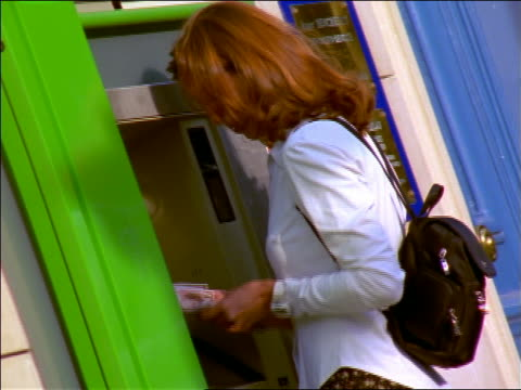 woman with backpack taking money + walking away from atm / france - 1999年点の映像素材/bロール