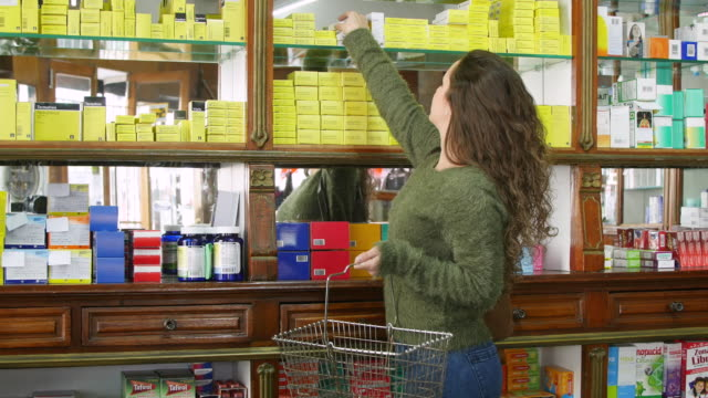 Woman with basket buying beauty products at store