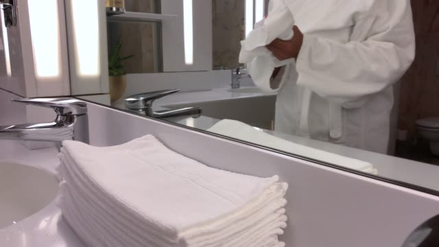 woman with bathrobe drying her hands with a towel - trocknen stock-videos und b-roll-filmmaterial
