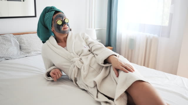 woman with beauty face mask in bathrobe lying on bed at home - human head stock videos & royalty-free footage