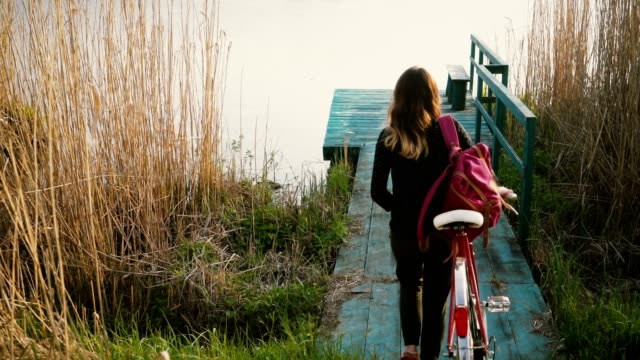 woman with bicycle near the lake - city break stock videos and b-roll footage