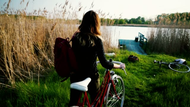 Woman with bicycle near the lake