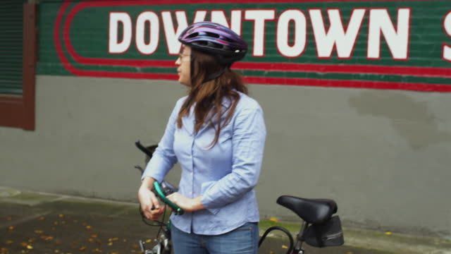 cu zi woman with bicycle wearing cycling helmet / portland, oregon, usa - portland oregon bike stock videos & royalty-free footage