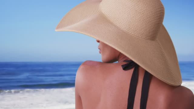 vídeos de stock, filmes e b-roll de woman with big sunhat looking out over ocean on vacation - hat