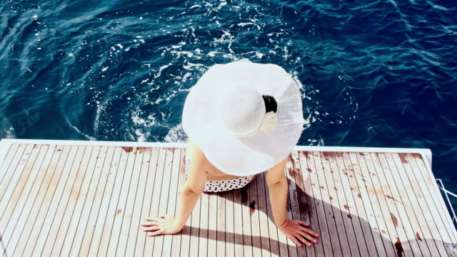 slo mo woman with big sunhat relaxing on the boat - sun hat stock videos & royalty-free footage